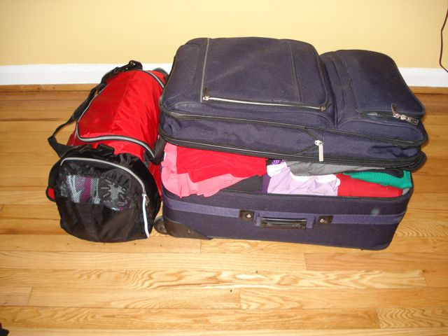 Red duffel bag and purple suitcase packed.